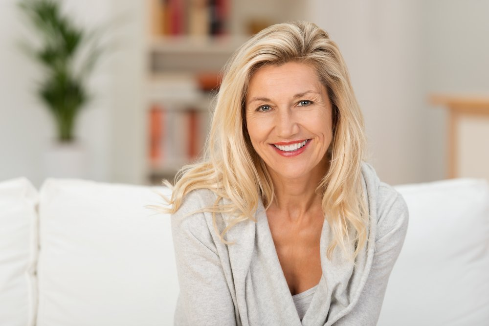Lovely middle-aged blond woman with a beaming smile sitting on a sofa at home looking at the camera